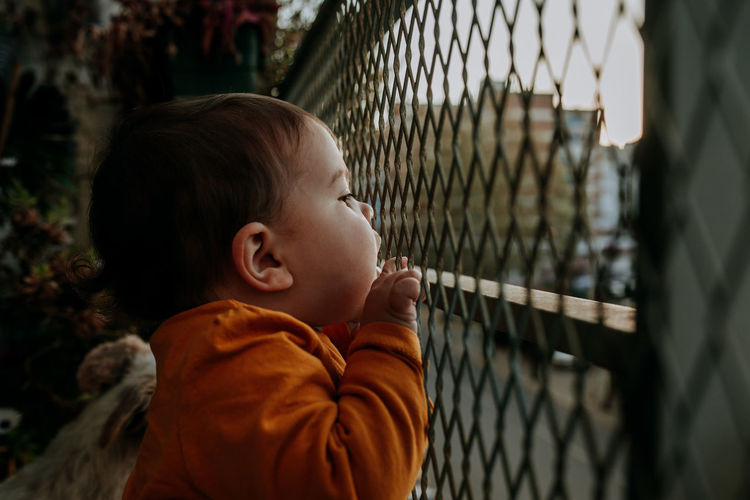 Fence Balcony Balcony View Protection Barrier Security Close-up Childhood Child Innocence Casual Clothing Portrait Cute Leisure Activity Lifestyles Boundary Looking Real People One Person Side View Orange Color My Best Photo
