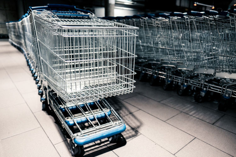 Cart Consumerism Convenience Focus On Foreground In A Row Indoors  Metal No People Retail  Shopping Shopping Cart Silver Colored Still Life Store Supermarket Tiled Floor Trolley Wheel