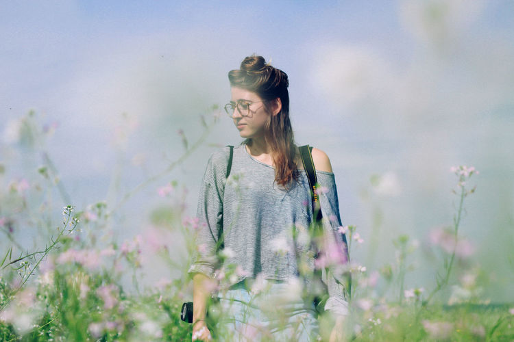 Young Woman In Meadow Against Sky