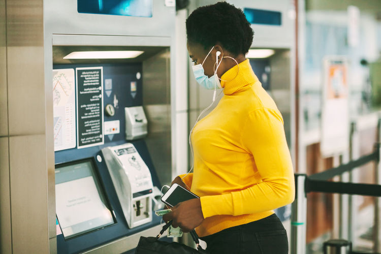 Dubai, uae, november 2020 african woman wearing a protective mask withdraws money from a bank card