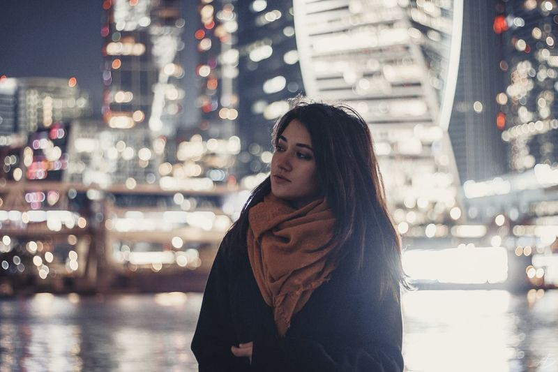 Young Woman Looking Away While Standing Against Illuminated Buildings At Night