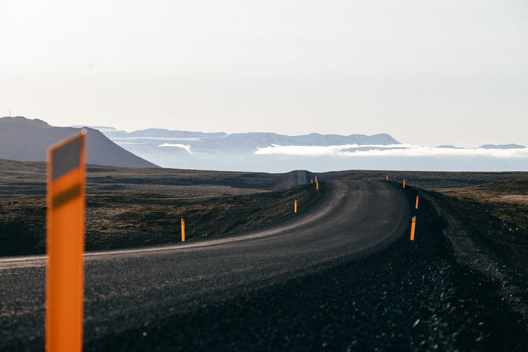 Empty road by mountain against sky
