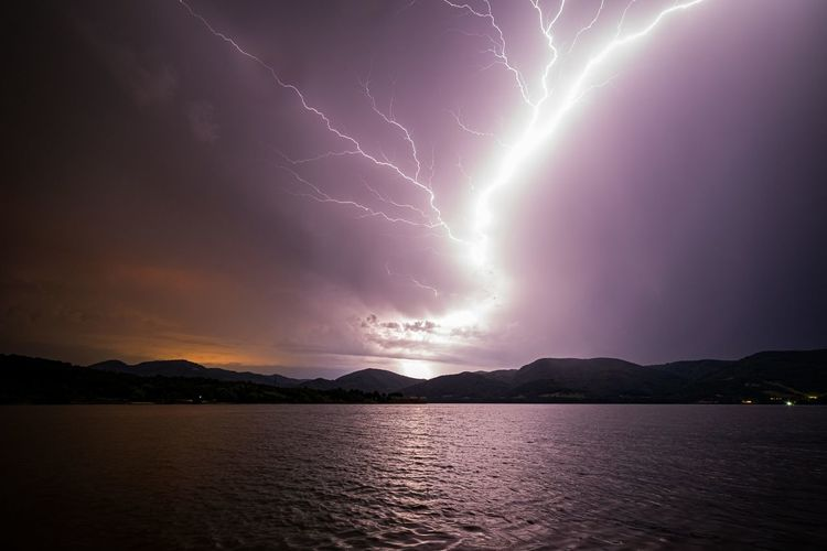 Scenic view of lightning over lake against dramatic sky
