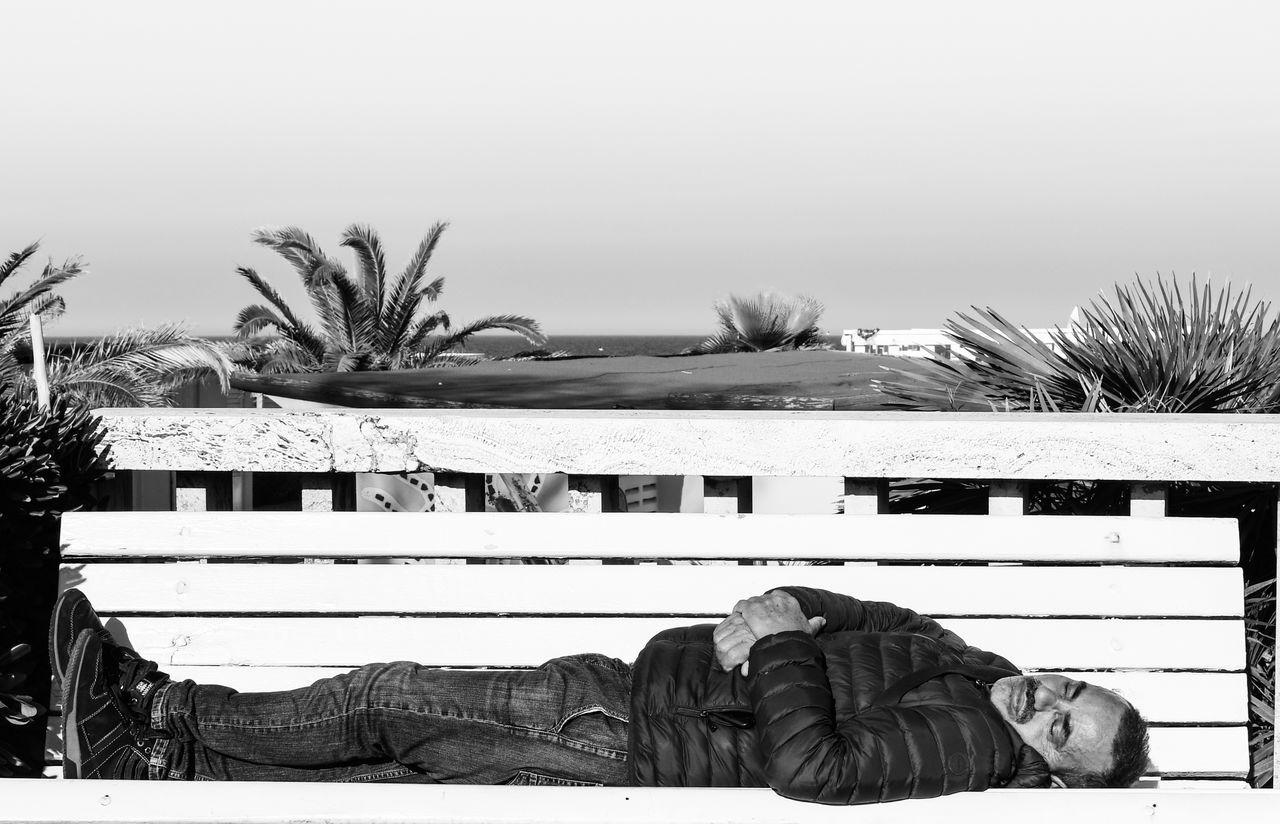 MAN SLEEPING BY HOUSE AGAINST SKY