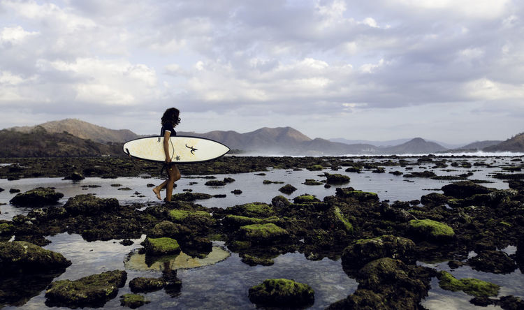 Female surfer at the beach Cloud - Sky Mountain Mountain Range One Person Photography Scenics Stones Surf Water