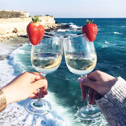 Close-Up Of Hand Holding Wineglass Against Sea