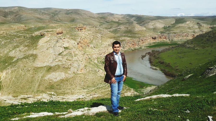 Full length portrait of mature man standing against landscape