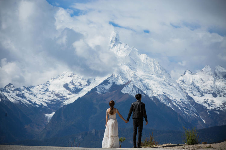Couple standing in front of snowcapped mountains against cloudy sky