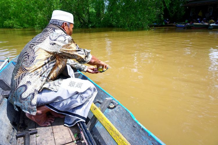 Offering for river dwellers Capture Tomorrow Water Tree Men Nautical Vessel Working Occupation Fisherman Sitting River