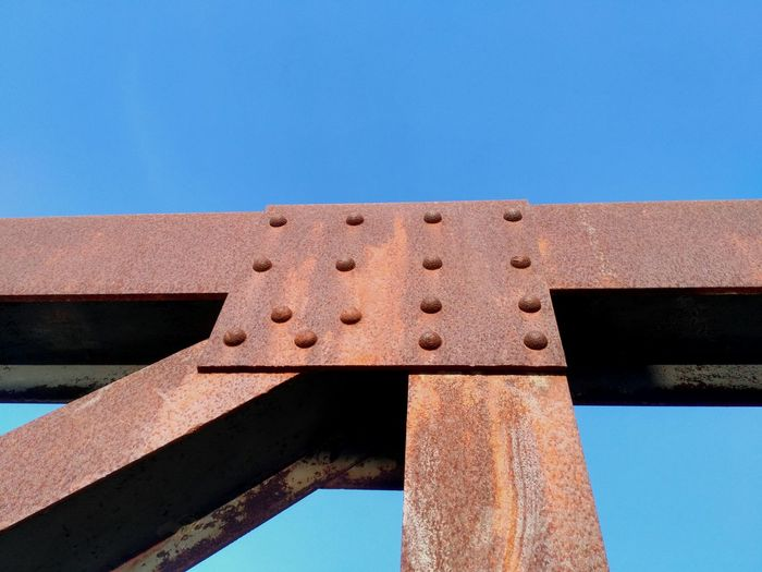 Low angle view of rusty bridge against clear blue sky