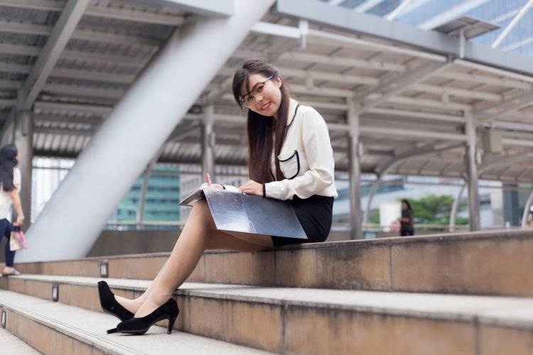 Portrait of businesswoman writing while sitting against office building