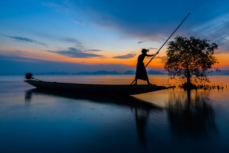Silhouette fisherman catching fish in the lake Agriculture Dramatic Sky Beauty In Nature Cloud - Sky Environment Fisherman Fishing Industry Lake Landscape Nature Nautical Vessel One Person Outdoor Outdoors Real People Reflection Scenics - Nature Silhouette Sky Standing Sunrise Sunset Tranquil Scene Tranquility Transportation