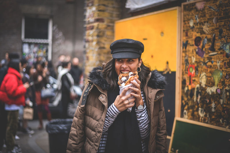 Young man holding ice cream standing in winter