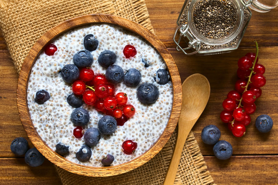 Chia (lat. Salvia hispanica) seed pudding with blueberries and redcurrants in wooden bowl, photographed overhead on wood with natural light (Selective Focus, Focus on the top of the pudding) Chia Dessert Meal Pudding Raw Salvia Hispanica Seed Snack Berry Berry Fruit Blueberry Breakfast Chia Pudding Currant Dairy Dairy Product Food Food And Drink Fresh Fruit Healthy Milk Raw Food Red Currant Uncooked