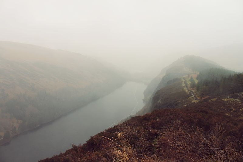 High Angle View Of River Amidst Mountains In Foggy Weather