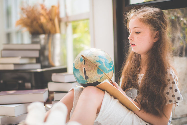 Cute girl looking at globe while sitting against window at home