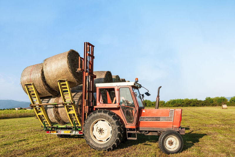 Tractor lifting hay bale on barrow.Agricultural landscape. Roll Rural Tractor Agricultural Machinery Agriculture Bales Countryside Farm Field Hay Landscape Nature Outdoors Round Rural Scene Sky Straw Tractor Trailer Transportation