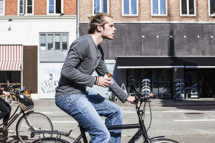 Side view of young man riding bicycle on street