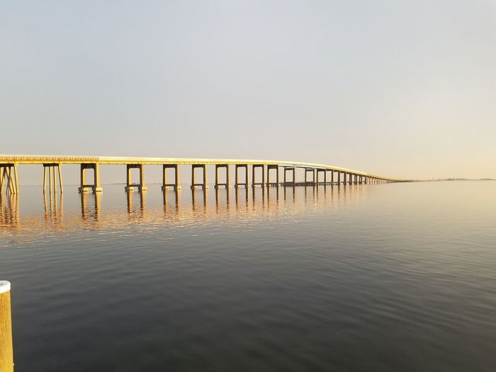 Golden sunset on Navarre Bridge, Florida, USA. Sunset_collection Sunset Silhouettes Reflections In The Water Reflection Sunlight Sunlight Reflection Sunlight And Reflection Sunlight Effect Sunlight Water Sea Clear Sky Beach Sunset Wooden Post Sunlight Copy Space Sky Horizon Over Water