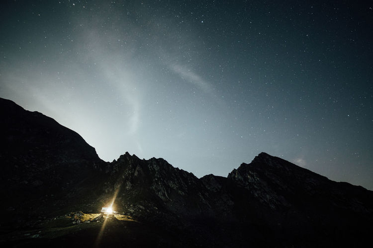 Light glowing on mountain against sky at night