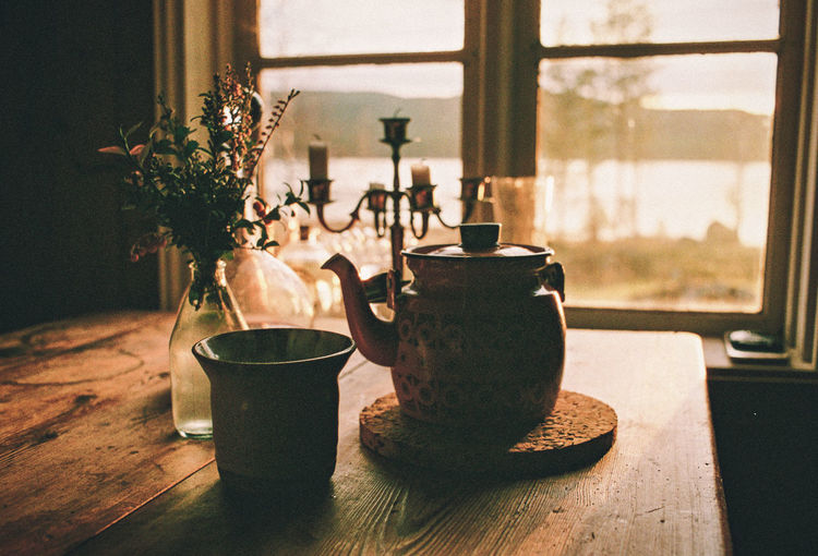 Close-up of tea cup on wooden table against window at home