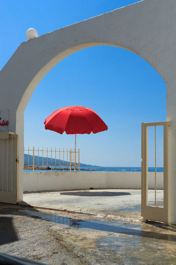 Red umbrella on beach against clear blue sky