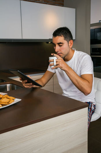 Young man having breakfast in the kitchen and looking at the tablet Vertical Copy Space Technology Comfortable Cozy Unmarried Enjoying Relax Sitting One News Modern Serious Portrait Biscuits Coffee Indoor Internet Real Clean Adult Alone Drink Young Concentrated Journal Sunday People Handsome Male Digital Web Lifestyle Husband Caucasian Home Kitchen Tranquility Morning Interested Tablet Reading Looking Breakfast Pajama Man Single
