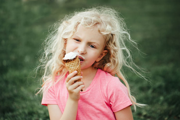 Girl eating licking ice cream from waffle cone. child eating tasty sweet cold summer food outdoor.
