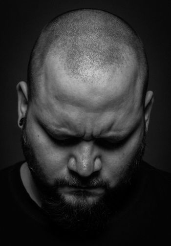 Close-up of angry man against black background