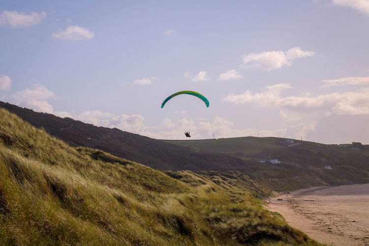 Scenic view of land against sky and paragliding