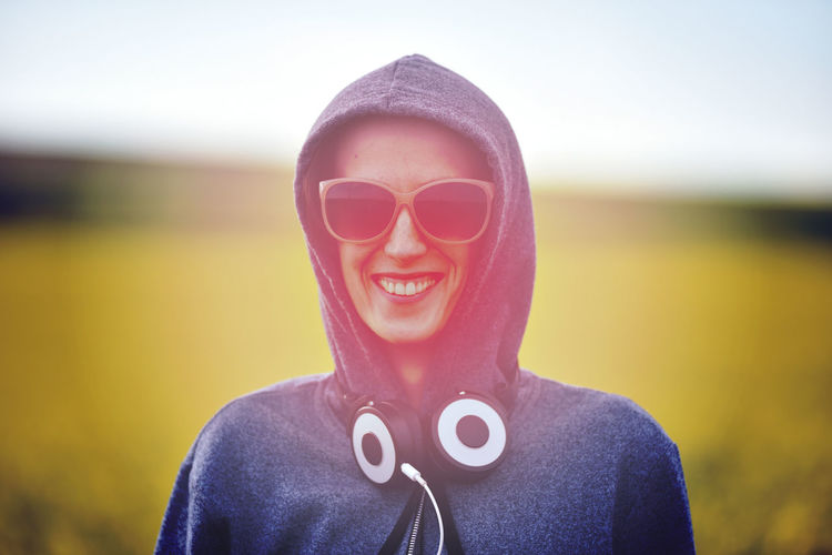 Hipster girl in hoodie, sunglasses and headphones in the outdoors Happy Headphones Laughing Positive Woman Beautiful Woman Cheerful Cheerfull Close-up Day Escape From The City Focus On Foreground Front View Happiness Headshot Hoodie Instagram Filter Leisure Activity Looking At Camera One Person Outdoors Portrait Real People Smiling Sunglasses