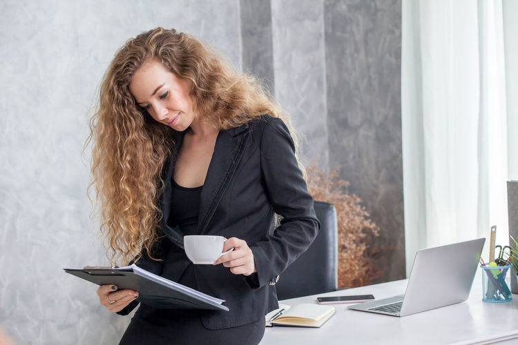 Businesswoman holding coffee cup while reading paper in office