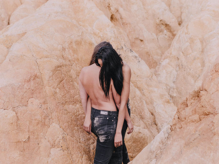 Rear view of woman standing on rock against wall