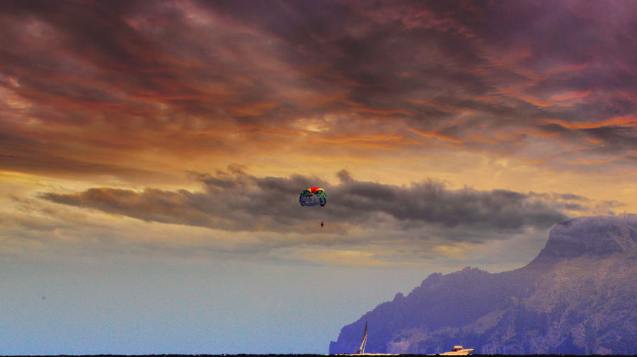Distant view of person parasailing in sky