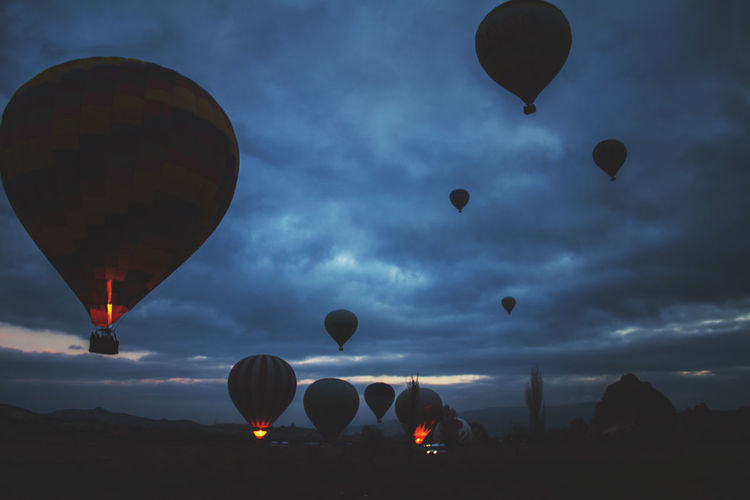 Low angle view of hot air balloons flying against cloudy sky at dusk