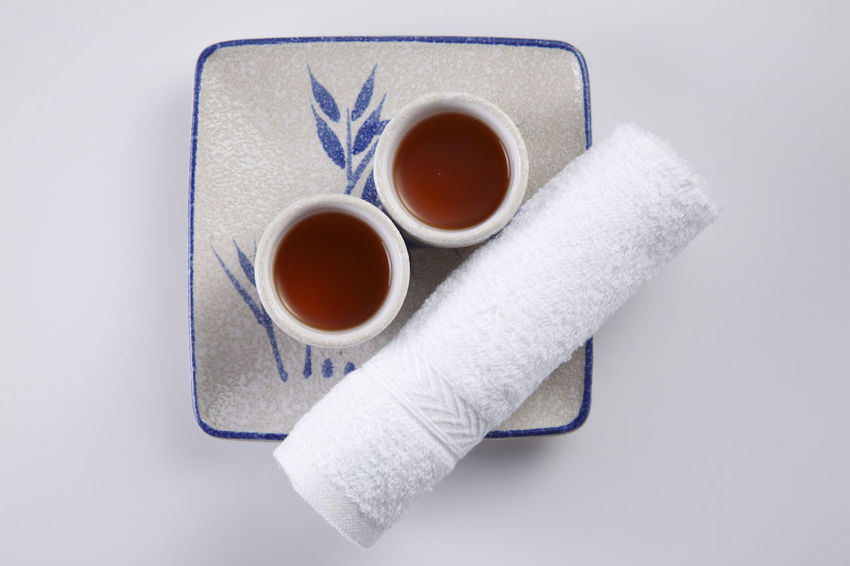 two cups of tea with rolled up towel Asian  Beverage Paint Rolled Up Served Service Tea Bamboo Close-up Day Directly Above Hot Towel Japanese Drink No People Oriental Plate Ready To Serve Spa Studio Shot Tea - Hot Drink Traditional White Background