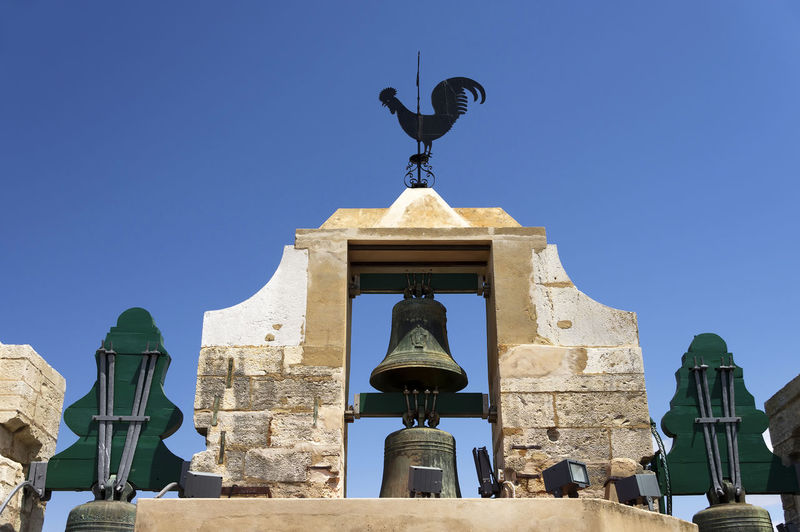 Low Angle View Of Bell Tower With Weather Vane Against Clear Blue Sky