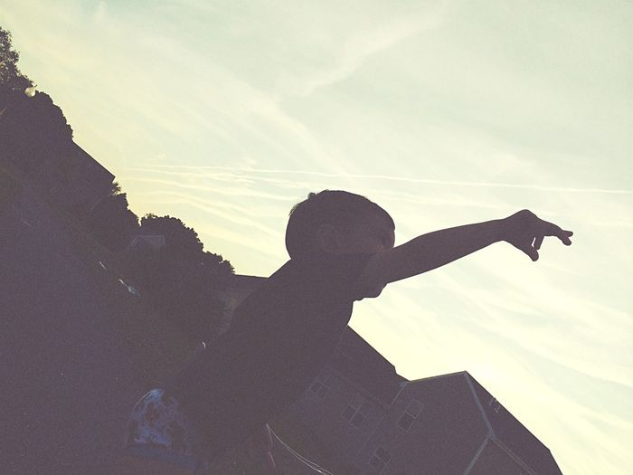 Boy Raising Hand In Lawn By House