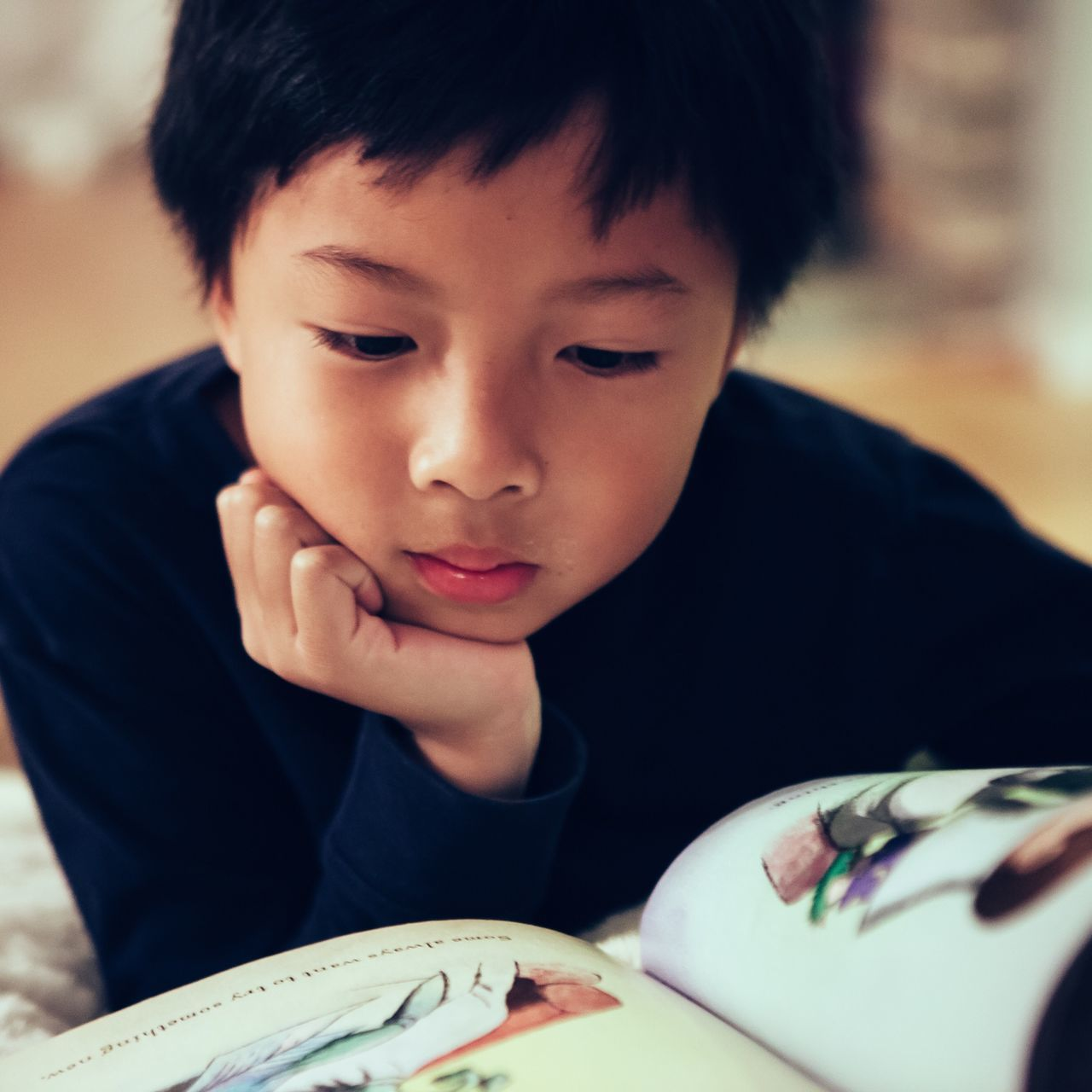 Cute boy with hand on chin reading book at home