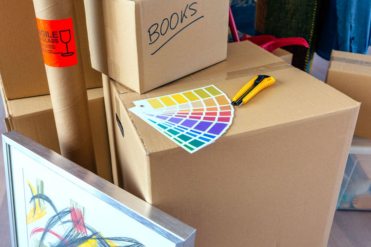 High angle view of color swatch with utility knife on cardboard box in new home