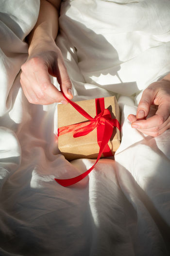 Girl unpacks a small gift in bed