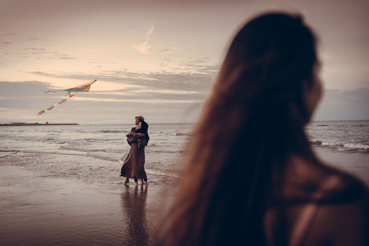 Rear view of woman on beach against sky during sunset with girls playing kite at the background