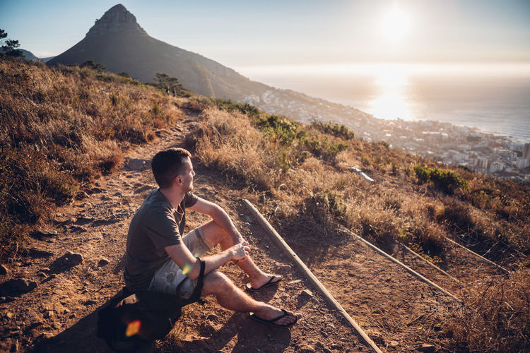 Man sitting on mountain against sky during sunset