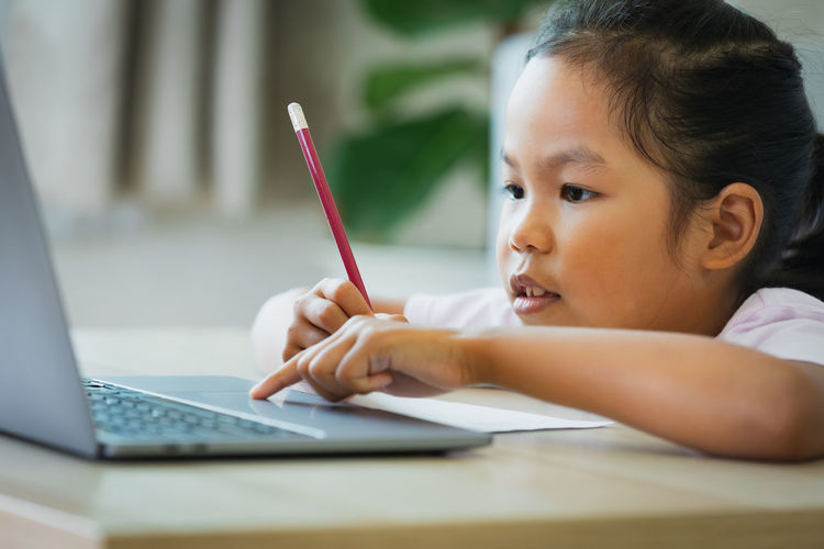 Portrait of girl with laptop on table