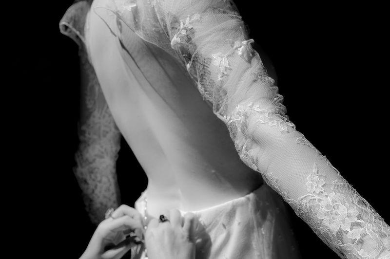 Cropped hands adjusting woman dress against black background