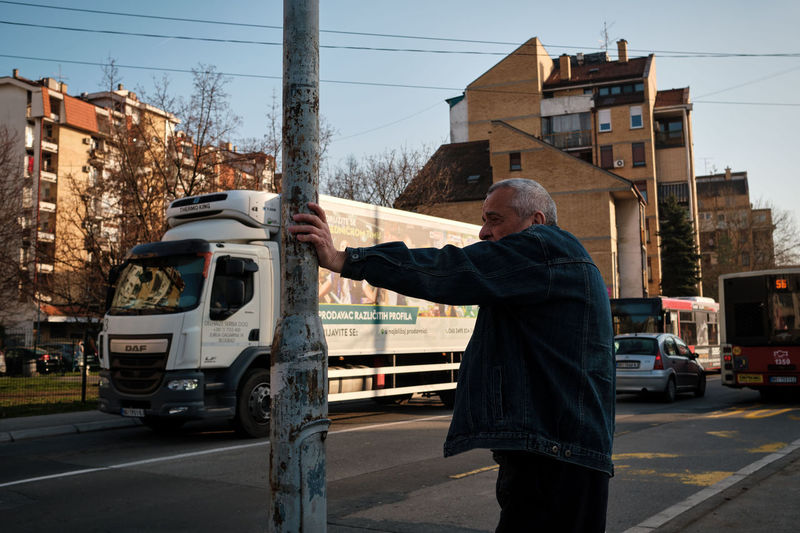 Man standing on road in city