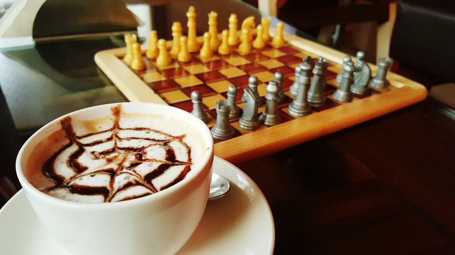 Cappuccino By Chess Board On Table