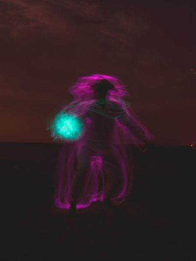 Blurred motion of woman standing against illuminated lights at night