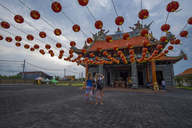 Benoa, Bali, Indonesia - January 28, 2017 : People praying and wishing a happy chinese new year on vihara satya dharma. Adult Architecture Building Exterior Built Structure Celebration Chinese Lantern Day Decoration Group Of People Incidental People Lantern Lighting Equipment Men Nature Outdoors Real People Sky Women