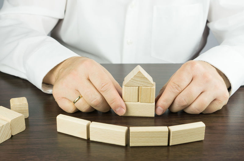 Midsection of man building house with wooden toy blocks at table